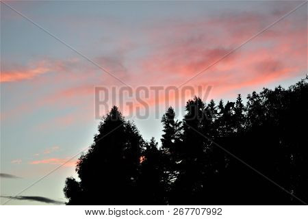 Clouds Glow Pink Against A Darkening Blue Sky Above A Backdrop Of Trees On A Summer Evening In Kentu