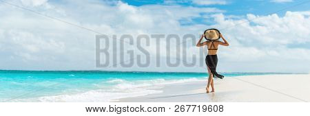 Luxury travel summer beach vacation woman walking in black beachwear skirt and hat on paradise white sand Caribbean beach. Lady tourist on Caribbean holiday vacation resort. Banner panorama landscape.
