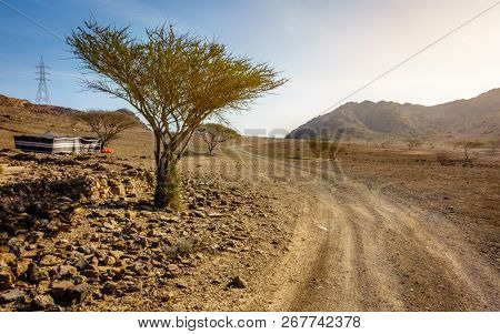 Dirt road in Al Hajar mountains in Fujairah, UAE and a tent
