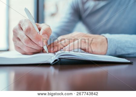 Man Hand Writing In Notepad. Agenda Or Scheduled Control Of Affairs.