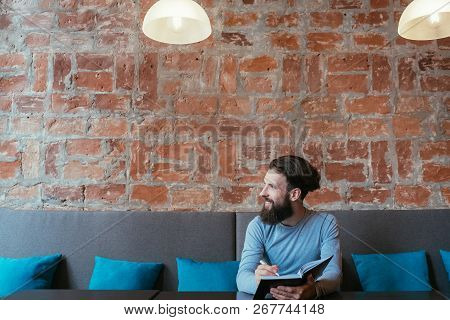 Man Writing In His Notebook. Planning Thinking And Ideas Visualization. Looking Away Waiting For Ins