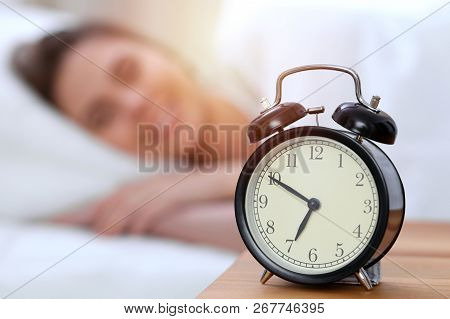 Alarm clock opposite of beautiful young woman sleeping while lying in bed comfortably and blissfully. Happy waking up early for a job poster
