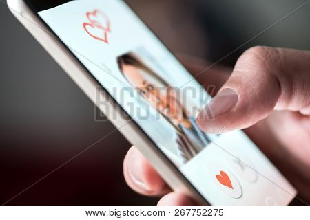 Online Dating App In Smartphone. Man Looking At Photo Of Beautiful Woman. Person Swiping And Liking