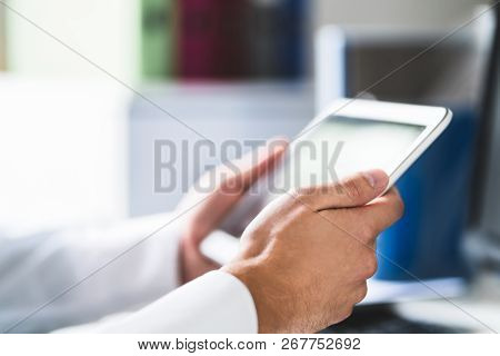 Doctor And Medical Professional Using Tablet At Work In Health Care. Physician Using Digital Electro