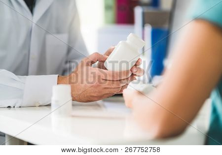 Doctor Consulting Patient About Right Medication. Physician Holding Medicine And Pills In Hand. Phar