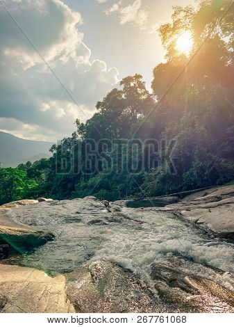 Beautiful Waterfall At The Mountain With Blue Sky And White Clouds And Orange Sun Light. Waterfall I
