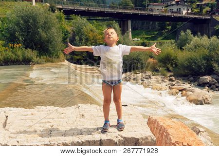 Boy Sunbathes On A Mountain River In The Summer On A Clear Day.