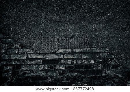 Old Shabby Dark Brick Wall With Fallen Off Plaster. Aged Weathered Brickwork Texture. Gloomy Grunge