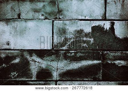 Old Cracked Concrete Blocks Wall. Huge Grain Bricks. Gloomy Grunge Background