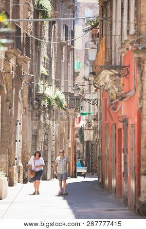 Taranto, Apulia, Italy - May 31, 2017 - A Tourist Couple Walking Through An Alleyway Of Taranto