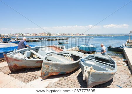 Taranto, Apulia, Italy - May 31, 2017 - Native Fishermen Working On Their Boats