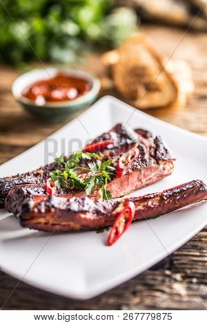 Tasty Barbecue Grilled Pork Ribs With Chili Pepers And Parsley Herbs.