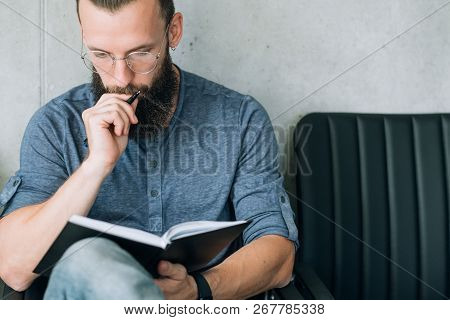 Focused Concentrated Man Reading Notes In Notepad. Data Analysis Or Business Strategy Development.