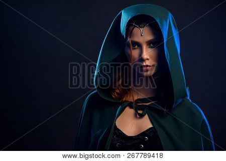 Portrait Of Young Charming Girl In Black Dress And Emerald Cloak With Hood On Her Head. Close Up Of