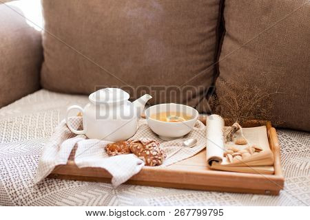 Mug Of Steamy Hot Beverage, White Teapot In Cozy Home Interior. Food, Drinks, Book Are On Wooden Ser