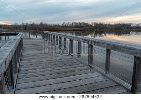Dramatic View From A Wooden Lake Dock Overlooking The Stillness On A Lake And Forest At Sunset In Au