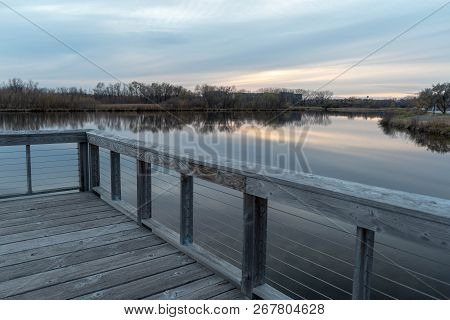 Dramatic View Of Still Lake Water From A Wooden Dock On A Misty Autumn Evening