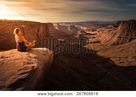 Woman Practicing Yoga Meditation At Sunrise. Beautiful Canyonland Landscape. Marlboro Point Dead Hor