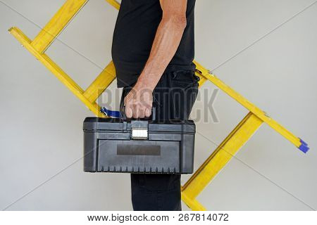 An Electrician Holds Tool Box And Yellow Wooden Ladder. The Builder Carries A Wooden Ladder And Tool