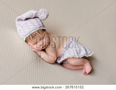 Cute little baby in knitted beanie and skirt sweetly sleeping on the light coverlet
