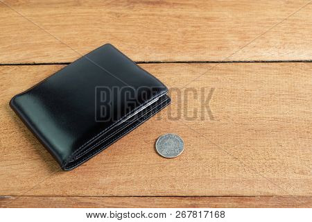 Black leather wallet with 5 baht coins on wooden floor, Insufficient expenditure poverty concept. poster
