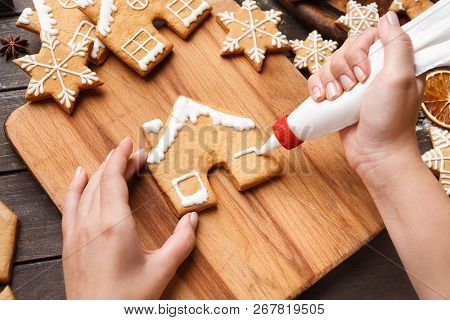 Christmas Bakery. Woman Hands Decorating Homemade Gingerbread House With Icing, Closeup