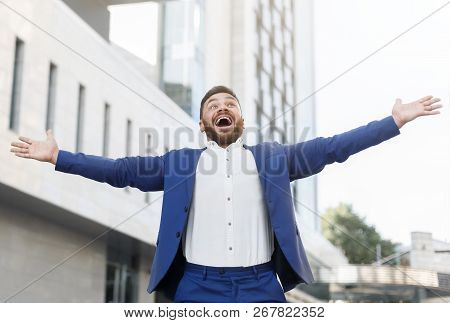 On The Top Of The World. Excited Businessman Creaming In Amazement, Outstretching Hands Outdoor