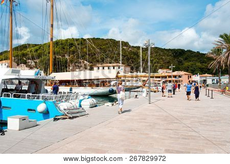 BONIFACIO, FRANCE - SEPTEMBER 19, 2018: People walking by the port of Bonifacio, in Corse, France, next to the yachts moored in the pier