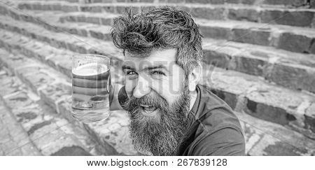 Guy having rest with cold draught beer. Hipster on happy face drinking beer outdoor. Friday relax concept. Man with beard and mustache holds glass with beer while sits on stone stairs poster