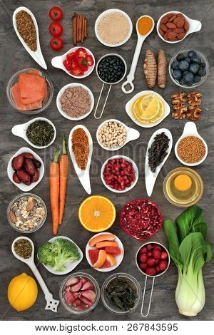 Food selection to slow the ageing process concept with superfoods very high in antioxidants, anthocyanins, dietary fibre and vitamins. Top view on marble background. poster