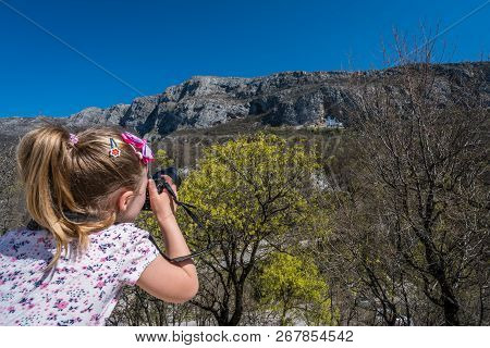Young Caucasian Girl Taking Pictures Of The Famous Landmark Ostrog Orthodox Monastery In Montenegro