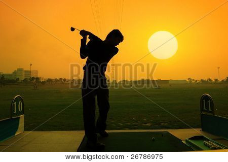 silhouette of a golfer on a bright sky