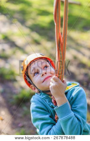 Smiling Boy Rides A Zip Line. Happy Child On The Zip Line. The Kid Passes The Rope Obstacle Course.