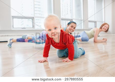 Baby Boy Crawling On Floor While Women Doing Workout In Gym Class To Loose Baby Weight. Child-friend