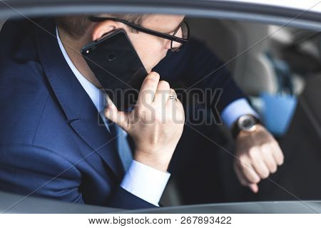 Young Successful Businessman Talking On The Phone Sitting In The Back Seat Of An Elite Car, Talks An