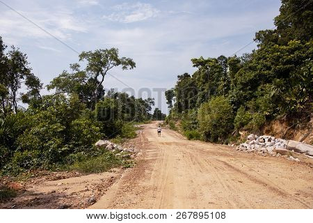Empty Road In Forest And Lonely Tourist. Road Construction Site In Green Nature. Tropical Island Dev