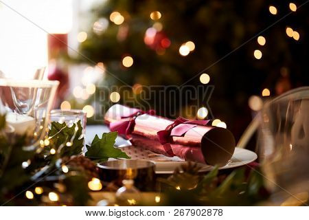 Close up of Christmas table setting with a Christmas cracker arranged on a plate and Christmas tree in the background