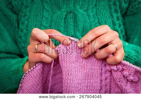 Close-up Of A Beautiful Woman In Knitting Green Sweater Knitting Needles From A Natural Woolen Threa