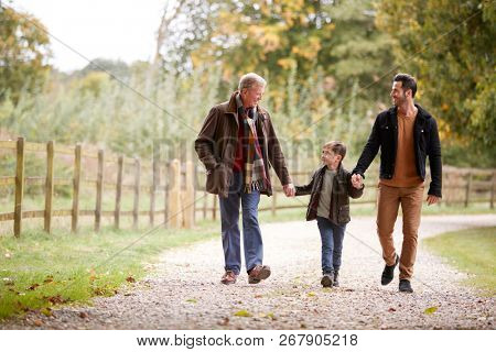 Grandfather With Son And Grandson On Autumn Walk In Countryside Together