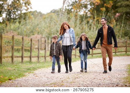 Family On Autumn Walk In Countryside Together