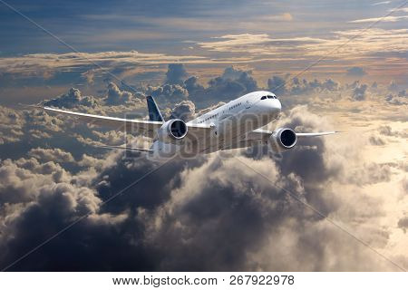 White Passenger Plane In Flight. The Plane Flies Against A Background Of Clouds And Mountain Landsca