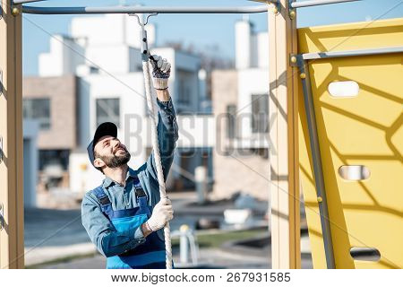 Handsome workman in uniform mounting rope for climbing on the playground outdoors poster