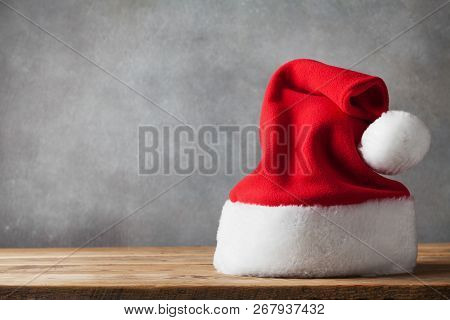 Christmas And New Year Concept With Santa Claus Hat On Wooden Background. Holiday Greeting Card.