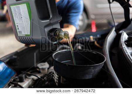 Car Mechanic Fills A Fresh Lubricant Engine Oil