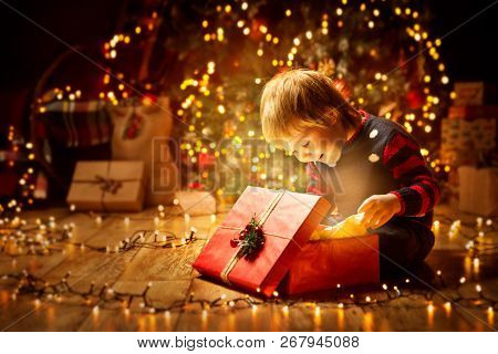 Christmas Child Open Present Gift, Happy Baby Boy Looking To Magic Light In Box, Kid Sitting Front O
