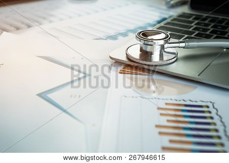 Stethoscope On Computer With Test Results In Doctor Consulting Room Background And Report Chart For