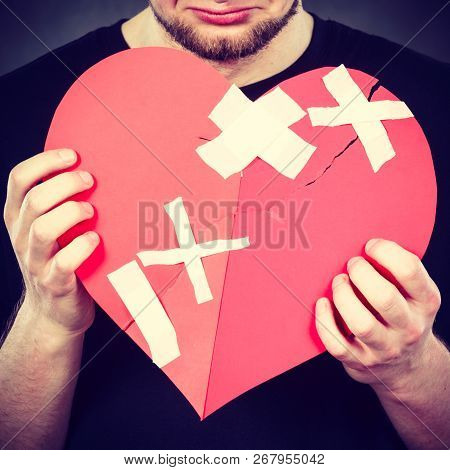 Bad Relationships, Breaking Up, Sadness Emotions Concept. Very Sad Young Man Holding Broken Heart Ma