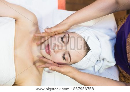 Beautiful Girl Enjoys Face Massage In Spa Salon. Procedures For Beauty And Rejuvenation. Thai Massag