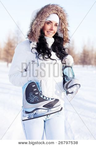 beautiful brunette girl wearing warm winter clothes going to ice skate poster