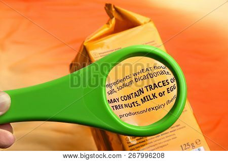 Magnifying Glass On Food Ingredients And Additives Label.  Reading Ingredients List On Food Package